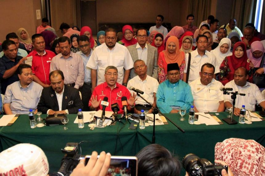 Kedah Umno deputy chairman Ahmad Bashah Md Hanipah (centre, in red) reading out a statement seeking Mr Mukhriz's removal at a press conference yesterday. Mr Mukhriz is accused of failing to unite the party leadership and not managing the state effect