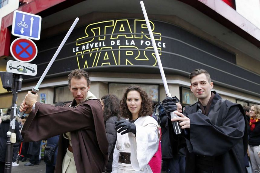 People dressed in costumes worn by Star Wars characters pose in Paris.