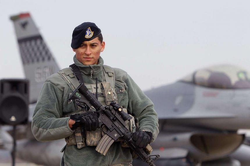 A US Air Force soldier stands guard in front of a fighter jet at Osan Air Base in Pyeongtaek, South Korea, on Jan 10, 2016.