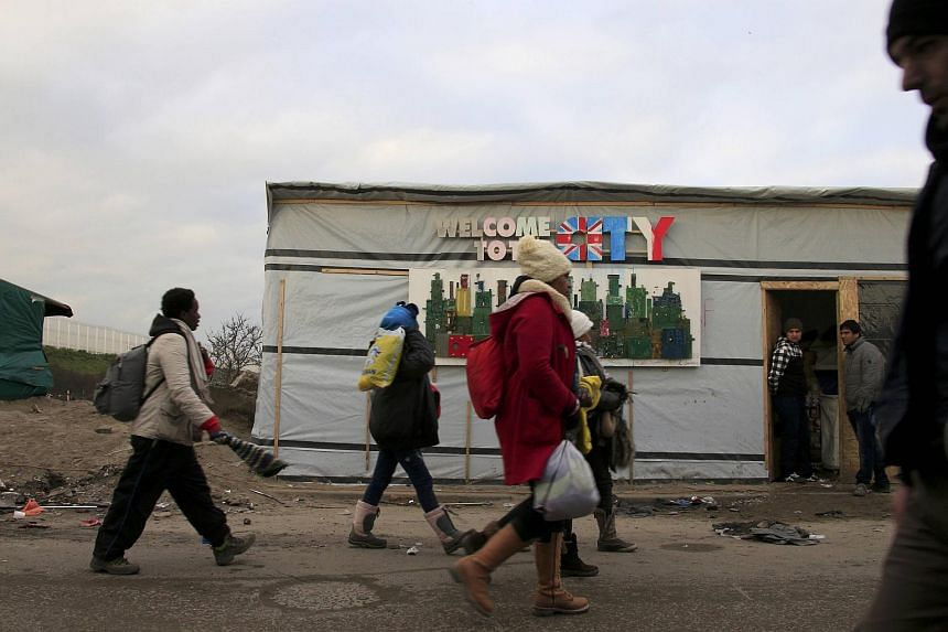 """Migrants walking past a grocery store in the """"Jungle"""" migrant camp in Calais on Jan 18."""