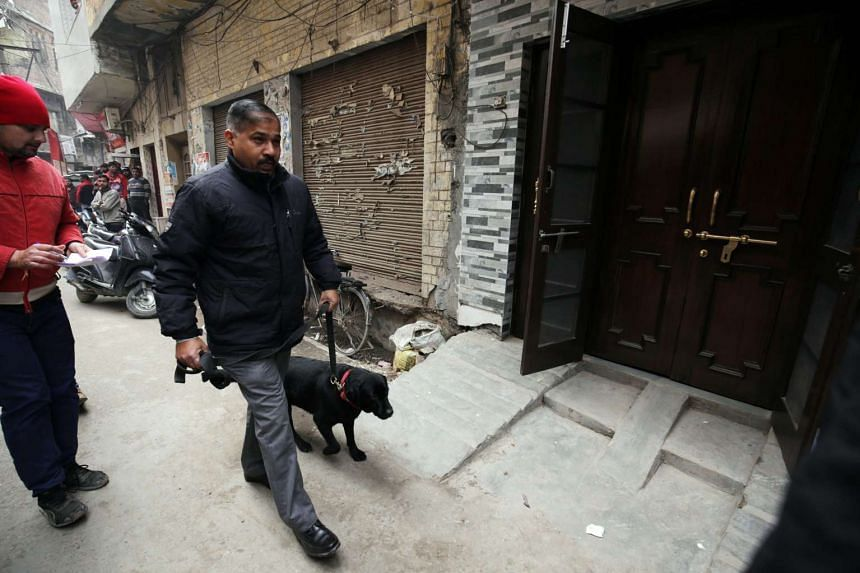 A National Investigation Agency (NIA) official with a sniffer dog arrives at a residence during a raid.