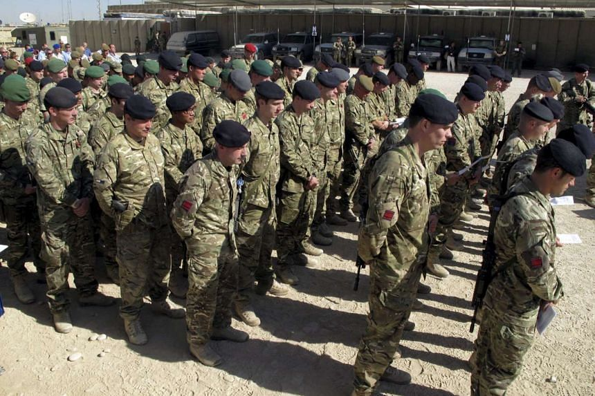 British soldiers observe a moment of silence during Britain's Veterans Day ceremony.