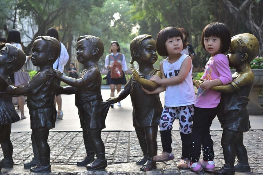 Children posed for photograph with bronze statues in Guangzhou city, China.