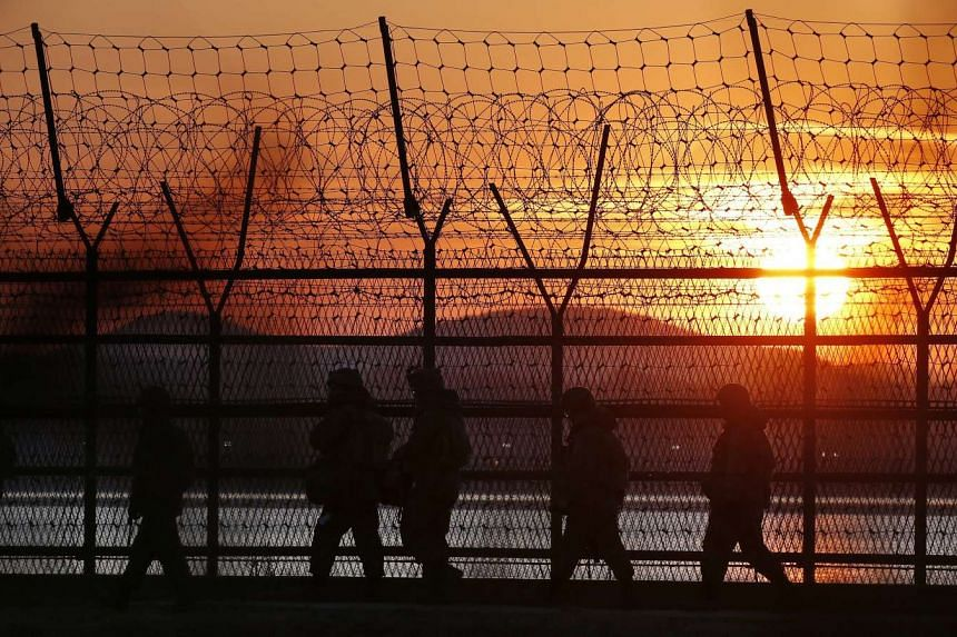 South Korean soldiers walk along a barbed wire fence near the inter-Korean border.