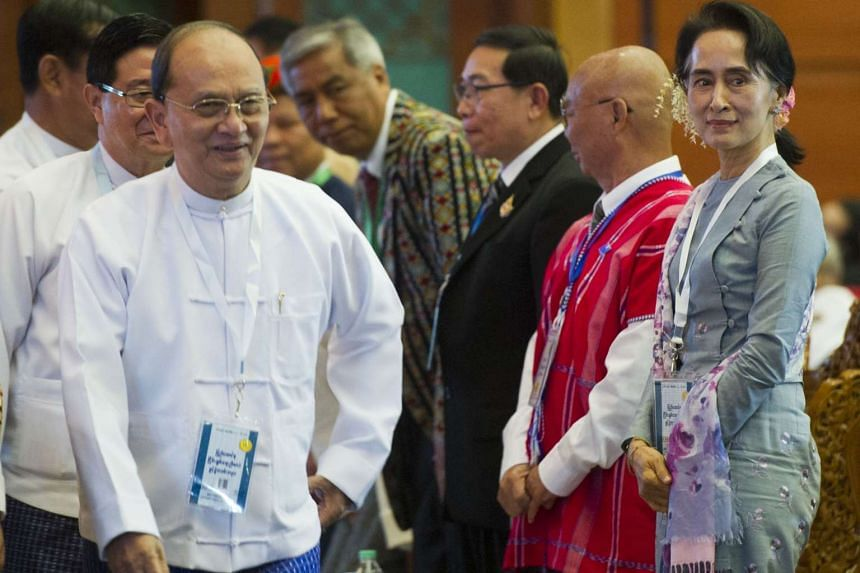 Myanmar President Thein Sein (left) walking past opposition leader Aung San Suu Kyi (right) during the opening ceremony of the Union Peace Conference in Naypyidaw on Jan 12.