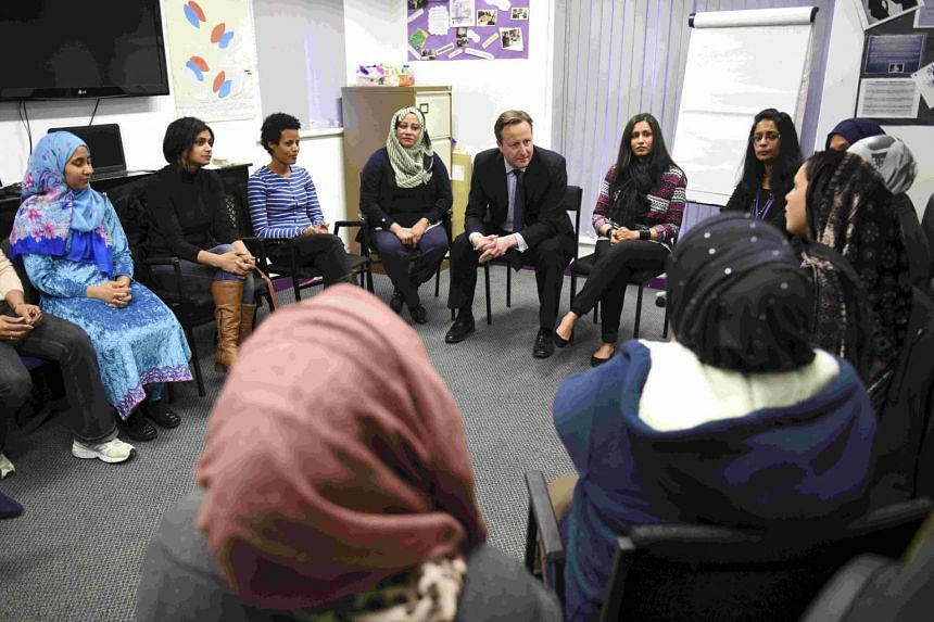 British Prime Minister David Cameron speaks with women attending an English language class at the Shantona Women's Centre in Leeds.