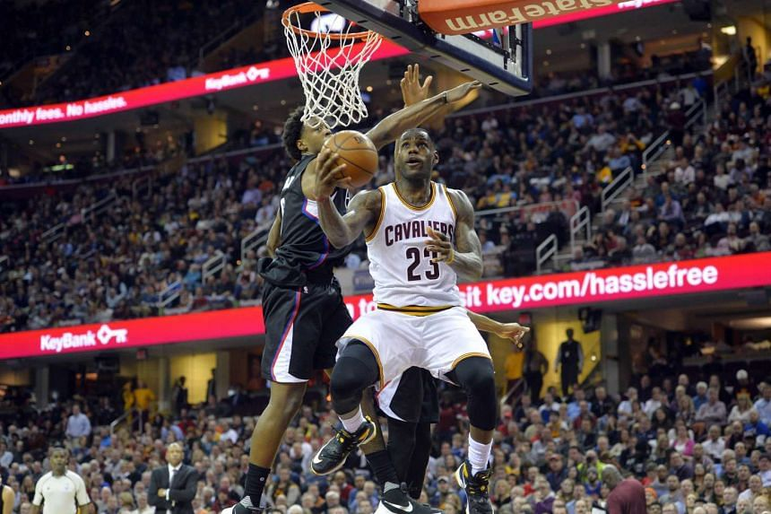 LeBron James (right) puts a reverse layup in the third quarter at Quicken Loans Arena.