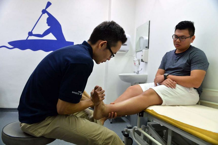 Dr Wang Mingchang treating full-time national serviceman Mr Cheong Hong Wei, 20, who has an ankle problem at the new NUH Sports Centre.