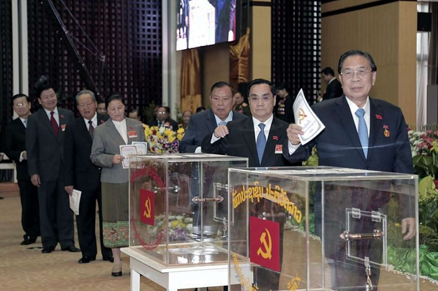 Laos President Choummaly Sayasone (right) and Prime Minister Thongsing Thammavong (second from right) cast their ballots on Jan 21, 2016.
