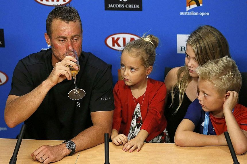 Australia's Lleyton Hewitt drinking champagne during a press conference after playing his last Australian Open match before his retirement. His children, (from left) Ava, Mia and Cruz, watch on.