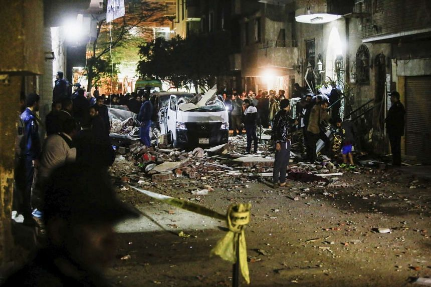 Egyptians stand at the scene of the explosion.