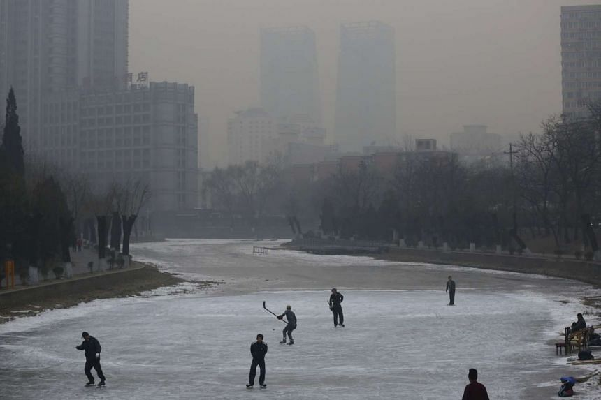 People skating on a frozen river in Beijing on Dec 29, 2015.