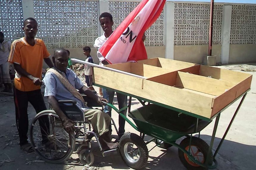 A disabled man receiving a cart so he can sell fruits and vegetables in Aden.
