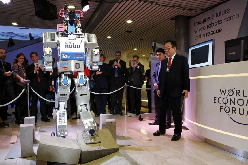 Hubo, a multifunctional walking humanoid robot, giving a demonstration of its abilities next to its developer, Professor Oh Jun Ho of the Korea Advanced Institute of Science and Technology, during the annual meeting of the World Economic Forum in Dav
