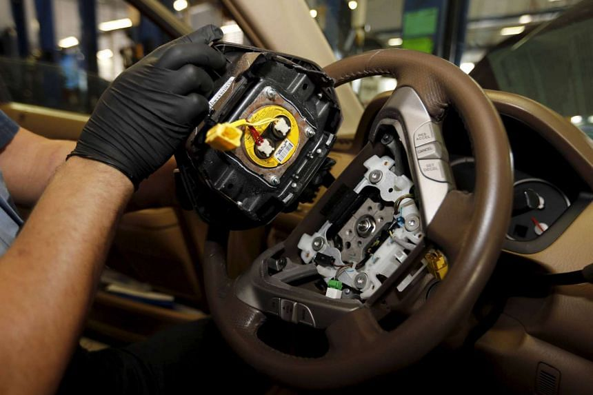A technician holding a recalled Takata airbag inflator at a Honda dealership's service department in Miami, on June 25, 2015.