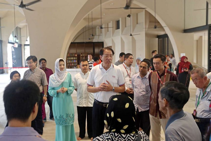 Pasir Ris-Punggol MP Sun Xueling (third from left) and DPM Teo Chee Hean (centre) speaking to Punggol residents on a guided tour of the Al-Islah Mosque on Jan 23.