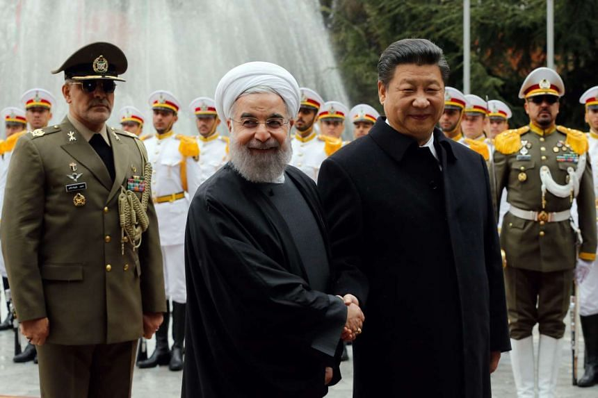 Chinese President Xi Jinping (right) with his Iranian counterpart Hassan Rouhani during a welcome ceremony at the presidential palace in Teheran.