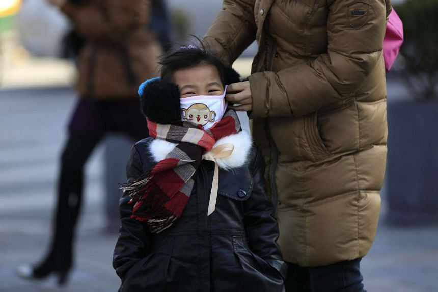 A woman adjusts the clothing of a Chinese girl to keep her warm in Beijing on Jan 23, 2016.