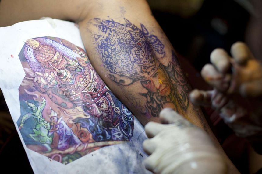 A tattoo artist practises his craft at the first Myanmar Traditional Ink Workshop on Jan 23, 2016.