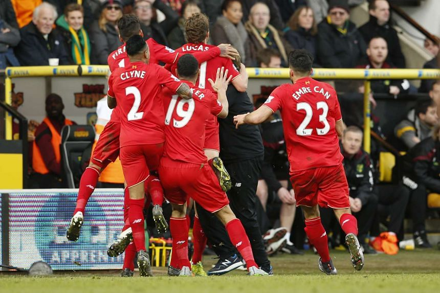 Adam Lallana celebrating with his Liverpool team-mates and manager Juergen Klopp after scoring the winning goal.