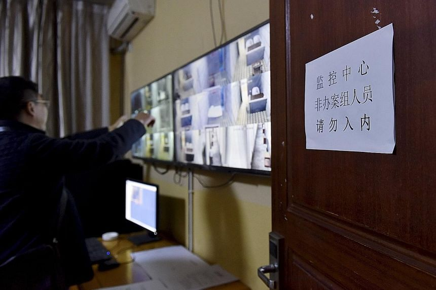 Officers look at monitors inside a surveillance room at a holding centre of the People's Procuratorate of Sichuan province for officials suspected of corruption. Critics say there is a lack of transparency around China's anti-graft drive and that it