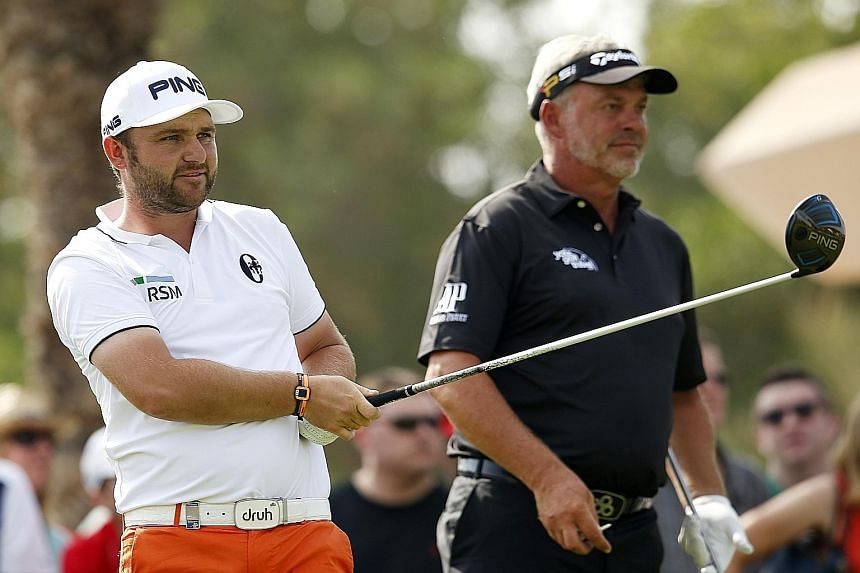 England's Andy Sullivan (left) teeing off at the 18th hole and being watched by Northern Ireland's Darren Clarke during the second round of the Abu Dhabi Championship.