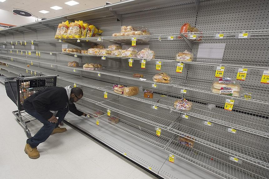 A customer at a severely depleted grocery store in Virginia on Thursday. Many people living in areas expected to be hit by the storm have begun stocking up on supplies.