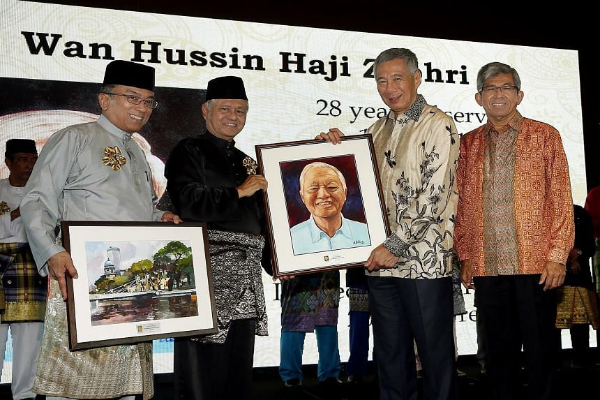 LBKM immediate past president Wan Hussin Zoohri (second from left) receiving a portrait of himself from PM Lee in recognition of his services. With them are current president Suhaimi (far left) andDr Yaacob.