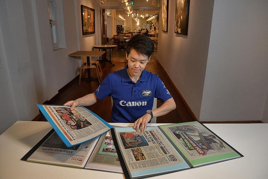 National bowler Shayna Ng with her folders of newspaper clippings at the Curious Palette on, Prinsep Street. Her aunt Margaret, who died last year, had been collating the files for more than 10 years.