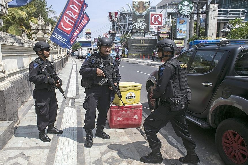 Indonesian anti-terrorism policemen standing guard yesterday at the 2002 Bali bombing memorial in Legian, Bali. Police have increased security on the resort island, following threats purportedly from militants linked to the group that attacked centra