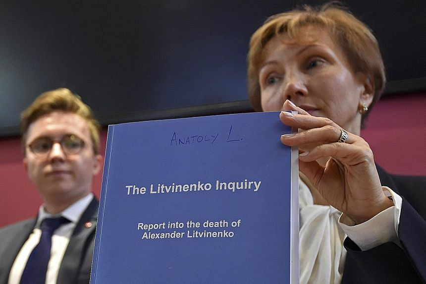 Ms Marina Litvinenko, widow of murdered former KGB agent Alexander Litvinenko, and her son, Anatoly, with a copy of the inquiry report on Thursday. Mr Litvinenko died of radiation poisoning in 2006 after drinking tea laced with radioactive polonium a