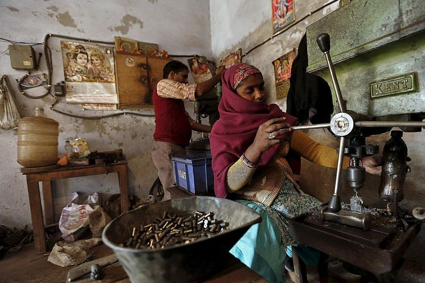 Labourers in small factories, such as this one in Faridabad, often toil for 12 hours a day to make parts for firms like Honda Motor and Yamaha Motor. PHOTO: REUTERS