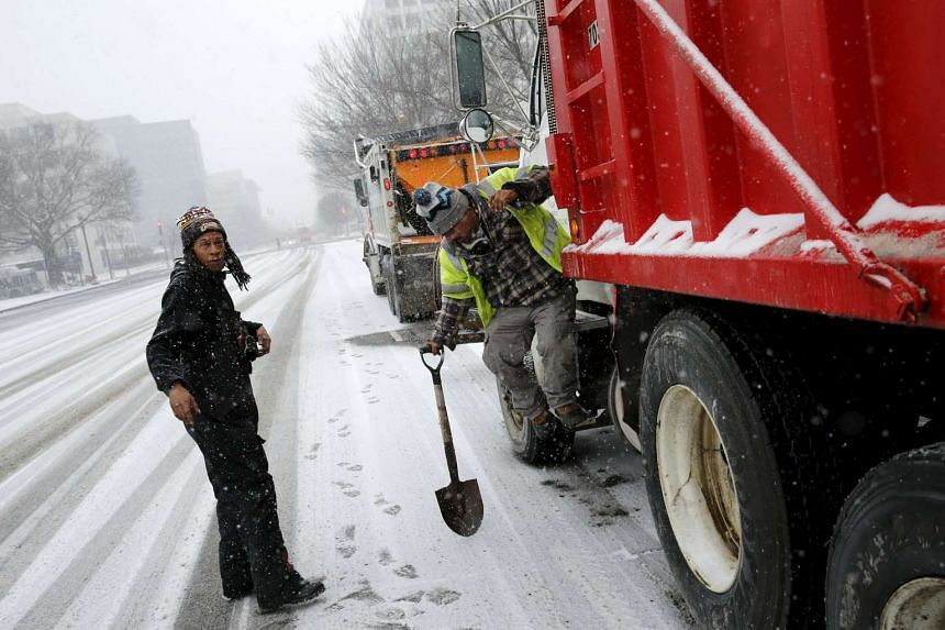 Crew members work on salt trucks as the snow begins to fall in Washington.