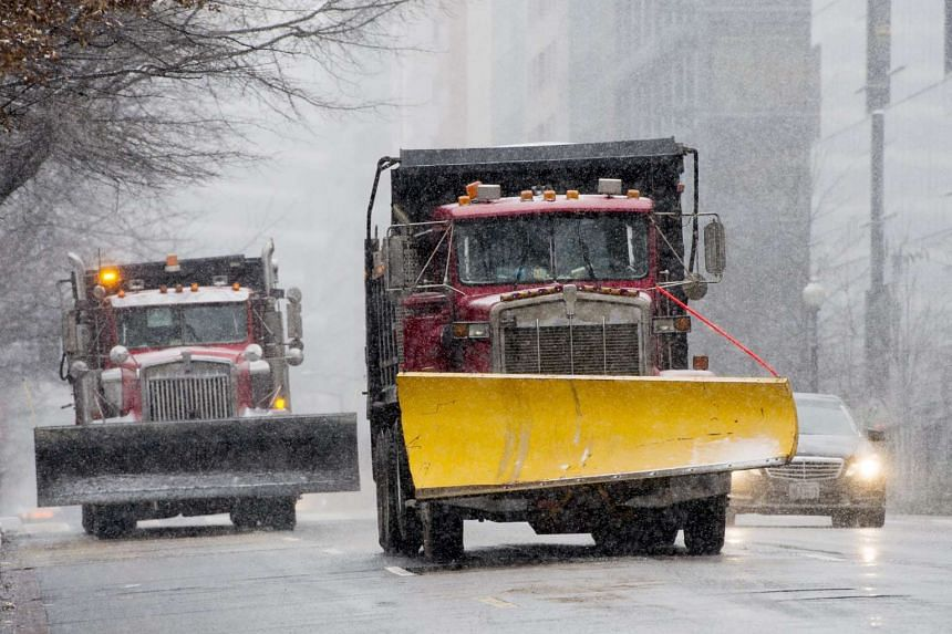 Snow ploughs drive down the street as the blizzard hits in Washington, DC.