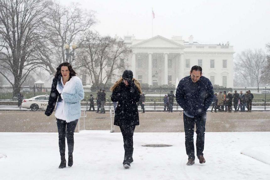 A woman (centre) shields her eyes as snow begins to fall at President's Park across the street from the White House.