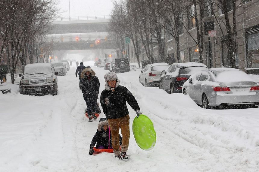A man pulls a child on a sled in Brooklyn with the Manhattan Bridge in the background during a large winter storm.