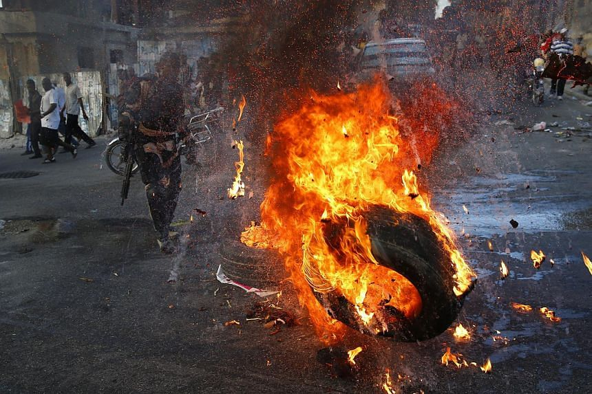 Demonstrators set tires on fire during protests demanding the resignation of Haitian President Michel Martelly, in Port au Prince, Haiti, on Jan 23, 2016.
