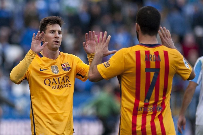 Lionel Messi (left) celebrates with Arda Turan after the 1-2 win in the Spanish league football match between Malaga CF and FC Barcelona.