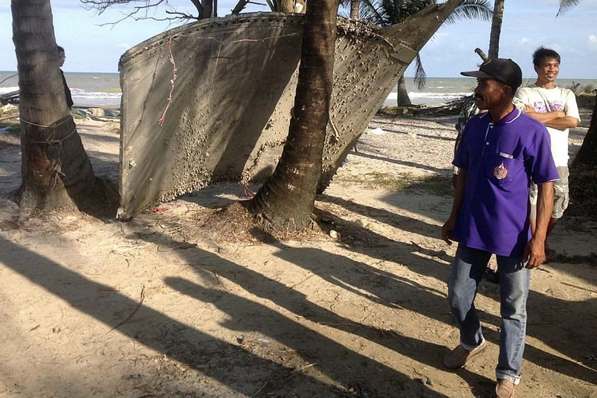 A Thai villager inspecting a piece of wreckage at a beach in Pak Phanang district, southern Thailand.