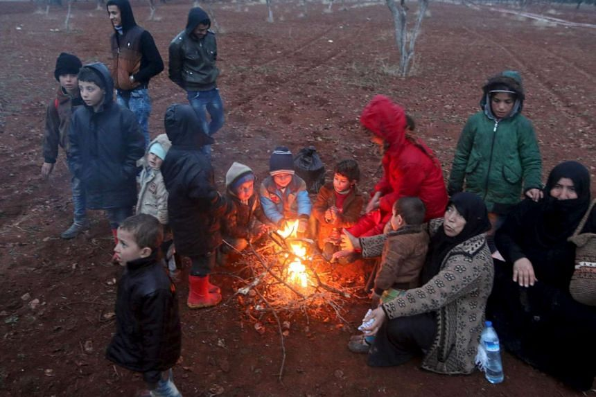 Displaced people warm themselves around a fire as they wait in the Syrian village of Akda to cross into Turkey.