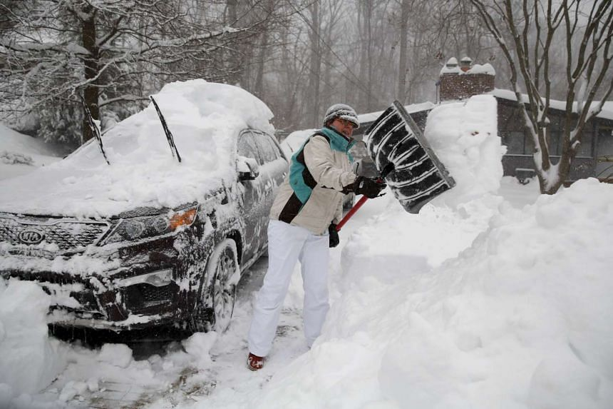 A woman digging her car out from under heavy snow in Falls Church, Virginia, on Jan 23, 2016.