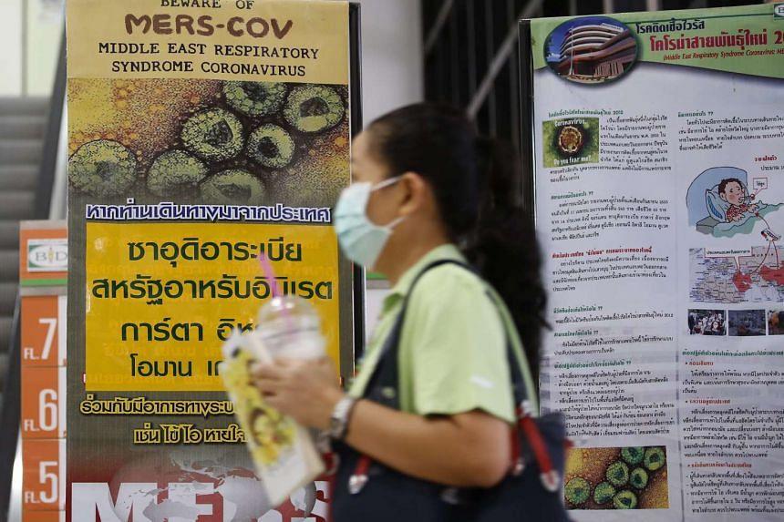 A woman wearking a protective mask walks past signs giving information on Mers in Bangkok on Jan 24, 2016.