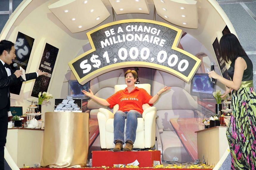 """Ms Linda Tobin sitting on the winner's seat after winning the """"Be a Changi Millionaire"""" draw on Jan 24, 2016."""