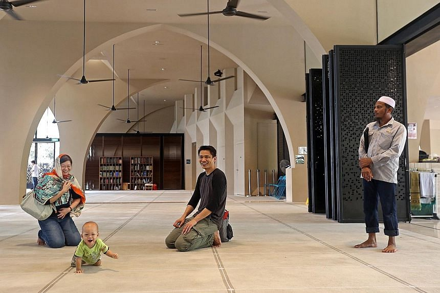 Punggol resident Sylvia Yap, her husband James Wong and their one-year-old son Yu Yong checking out the prayer hall of Al-Islah Mosque with congregant Mohammed Jahangiralam (right), during a guided tour for residents of all races and religions yester