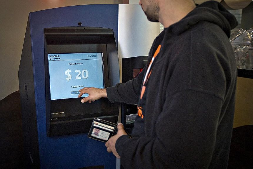 A fight has broken out between bitcoin developers who want to expand its commercial potential and those who want to protect its status as a challenger to currencies. Above are a bitcoin mining machine and a paper wallet with QR codes. A customer usin