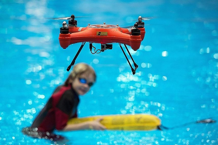 A waterproof Splash drone hovering in mid-air after dropping a rescue package for a child in a pool during its press debut at the water sports event Boot in Duesseldorf, Germany. Boot is the world's largest trade fair for the industry, covering saili