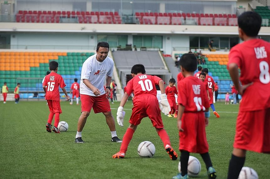 Local football great Fandi Ahmad and other former Lions teaching the youngsters the finer points of dribbling and passing.