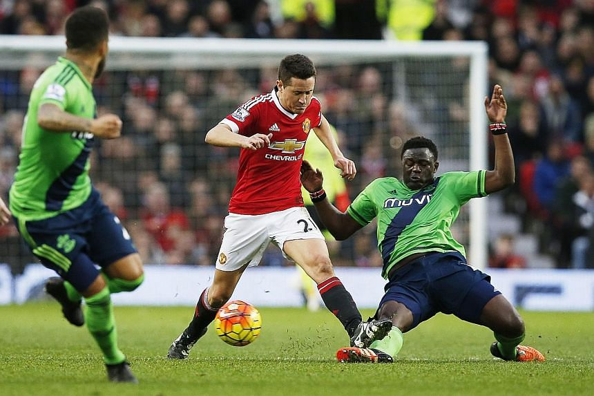 Southampton's Victor Wanyama (right) tackling Manchester United's Ander Herrera during their English Premier League clash at Old Trafford yesterday. An 87th-minute header by new signing Charlie Austin gave the Saints a shock 1-0 victory, and heaped m