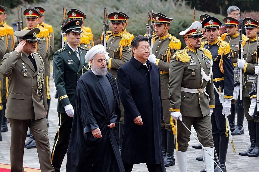 Iranian President Rouhani and his Chinese counterpart, Mr Xi, at a welcome ceremony at Iran's presidential palace in Teheran yesterday. Mr Xi is the first Chinese president to visit Iran in 14 years.