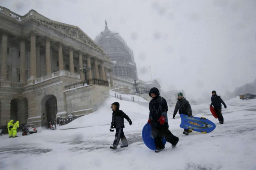 Kids carry their sleds in the falling snow outside the US Capitoi in Washington.